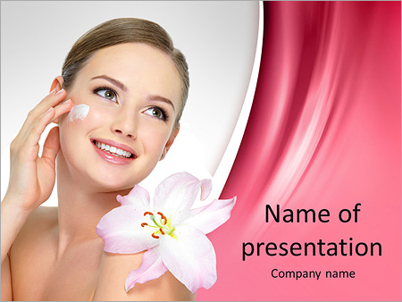 Happy portrait of beautiful young woman with flower on a shoulder applying cosmetic cream on a cheek PowerPoint Template